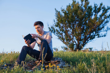 man sitting on a hill and reading a book
