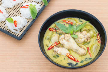 Chicken green curry with Rice vermicelli on wooden background
