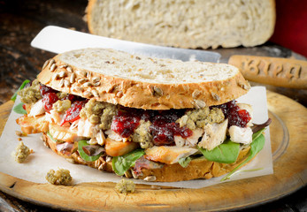 Turkey, chicken sandwich with stuffing and cranberry sauce.