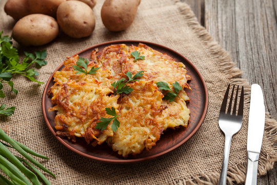 Homemade traditional potato pancakes or latke Hanukkah celebration food in rustic clay dish on vintage wooden background