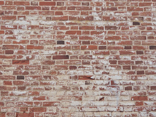 Old red brick wall with shabby paint.
