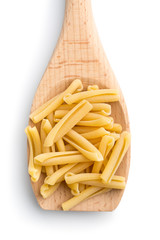 uncooked pasta caserecce in wooden spoon