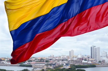 Colombian flag waving on the wind and modern Cartagena district