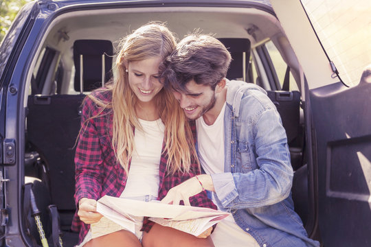 young lovers looking map sitting in the trunk of car