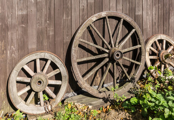 Three old wagon wheels with metal rims leaning against a wall of wooden planks