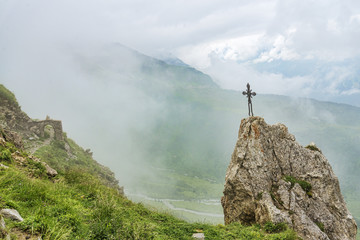 Metal Christian cross on rock and old stone building among alpine landscape