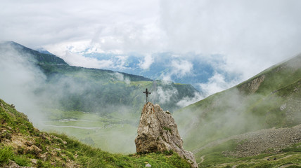 Christian cross mounted on rock in mountains
