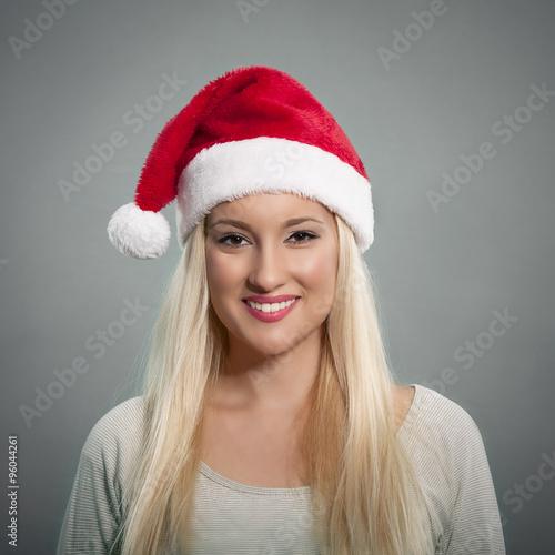 5140ebddcf4d2 Beautiful young woman wearing Santa hat posing against gray background