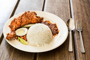 Delicious Nasi Lemak with fried chicken on wooden table