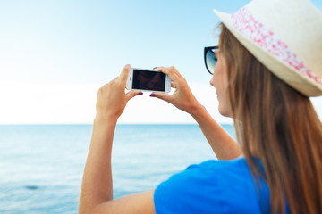 Girl in hat making photos of the Adriatic sea by the smartphone