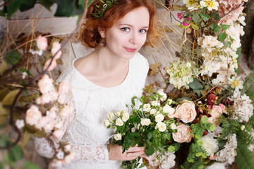 Young red-haired bride in a green wreath is holding a bouquet of white roses and gently smiles. She is surrounded by flowers and plants.