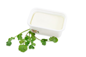 Container of feta cheese and a branch of a coriander