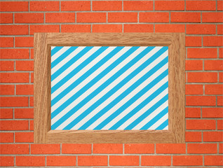 Old frame with striped canvas on orange brick wall