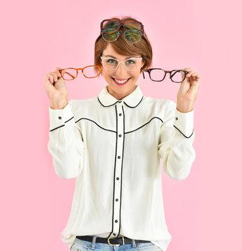Cheerful trendy girl having trouble choosing eyeglasses