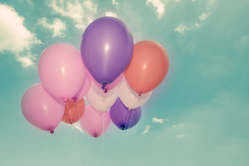 Colorful balloons on blue sky background in vintage color style
