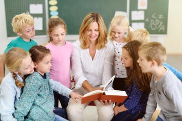 frau liest kindern in der schule etwas vor