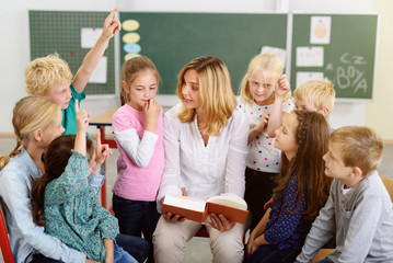 kinder und lehrerin in der grundschule besprechen ein buch