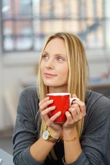 frau trinkt eine tasse tee und schaut in gedanken nach oben