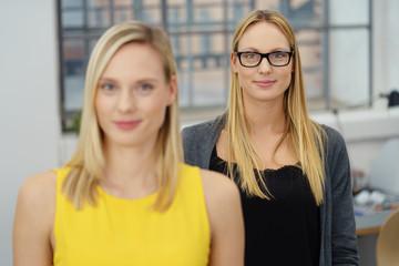 zwei junge geschäftsfrauen stehen im büro