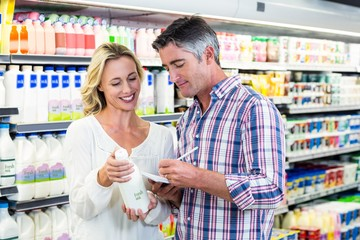 Smiling couple buying milk and checking list