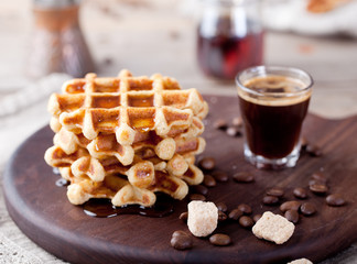 Fresh waffles with maple syrup and coffee