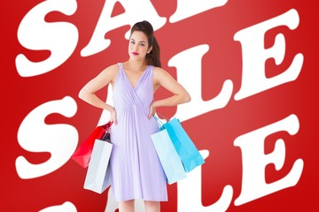 Composite image of elegant brunette with shopping bags