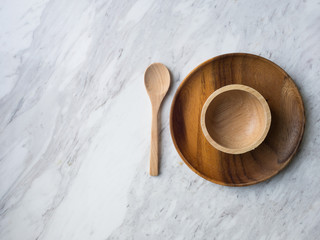 Wooden Spoon and plate on white marble.