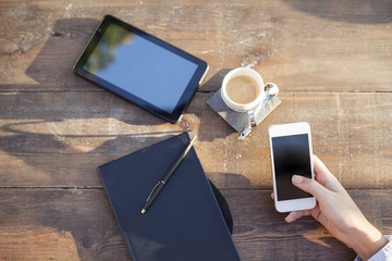 Cup of hot coffee, digital tablet, note book and woman hand using smartphone on wood table background