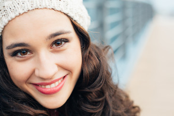 Cute young woman with woolen cap smiling