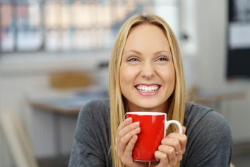 lachende frau hält eine tasse tee in der hand