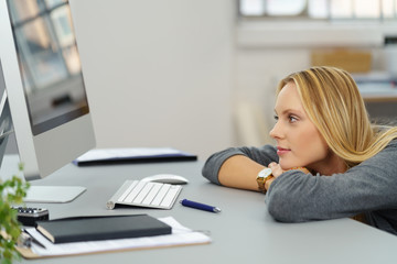 frau im büro legt kopf auf den schreibtisch und schaut auf computer