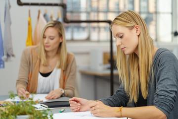 zwei junge frauen arbeiten in einem atelier für modedesign