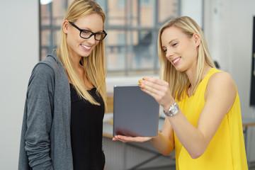 frau zeigt einer kollegin einen entwurf am tablet