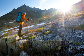 Young man is hiking in highlands of Altai mountains, Russia