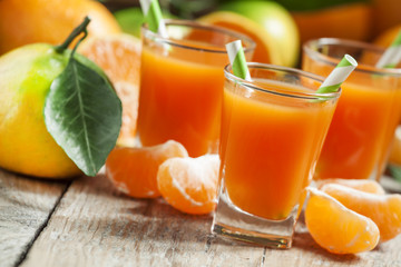 Fresh juice of ripe mandarins in a small glass with striped stra