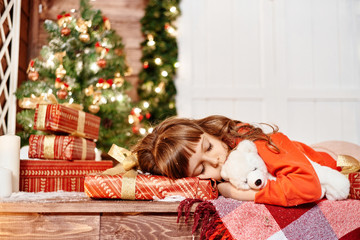 Little girl sleeps with a toy-bear on the porch of house at  Christmas tree.
