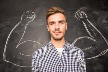 Young  man against the background of depicted muscles on chalkbo