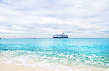 Cruise ship and tender on a light blue sea at Half Moon Cay in t