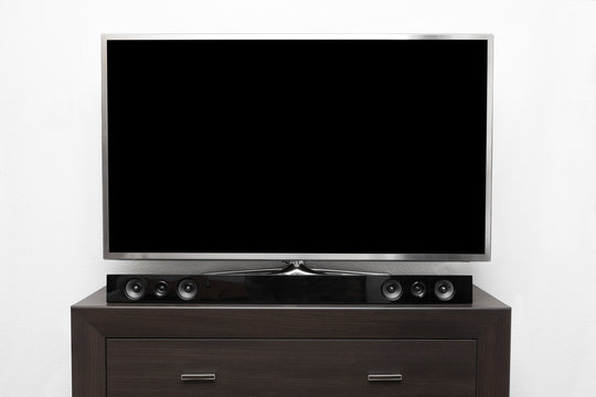 big tv with blank screen on brown commode at white wall