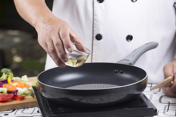 Chef pouring vegetable oil to the pan