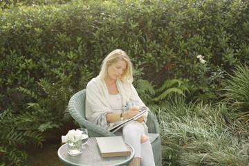 Blond woman sitting in a wicker chair in a garden, writing.