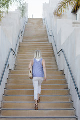Blond woman walking up a staircase.