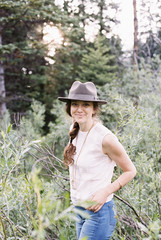 Smiling woman wearing a hat standing in a forest.