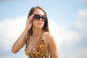 portrait of glamor young woman in leopard color swimsuit in sunglasses