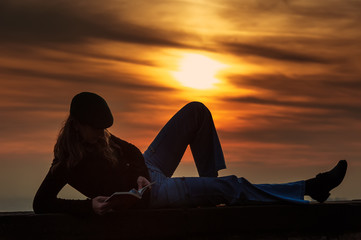 Girl reading a book on the wall at sunset