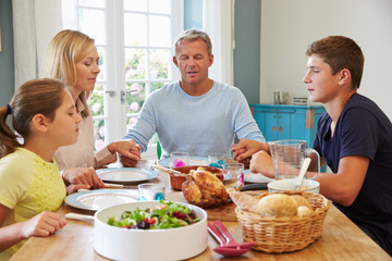 Family Saying Prayer Before Enjoying Meal At Home Together