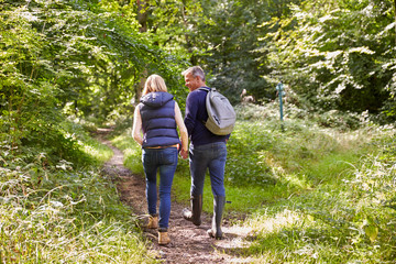 Mature Couple On Walk Through Beautiful Countryside
