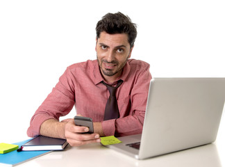 businessman working at office desk texting with mobile phone in front of computer laptop smiling  happy