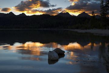 Two rocks in lake at sunset.