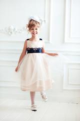 Laughing kid girl 4-5 year old having fun in room. Looking at camera. Childhood. Wearing stylish white dress.